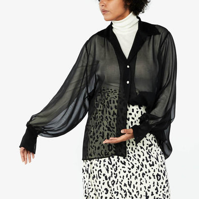 Black sheer shirt with balloon sleeves and white buttons.
