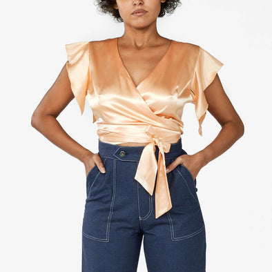 Light orange satin crop top with flowy sleeves.