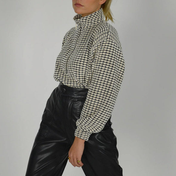 Oversized pullover in warm checkered black and grey mesh, with high collar and metallic closure.