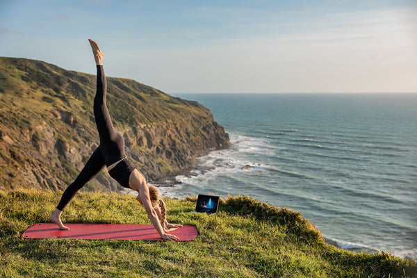 Woman practicing Yoga on top of a mountain overlooking the sea.
