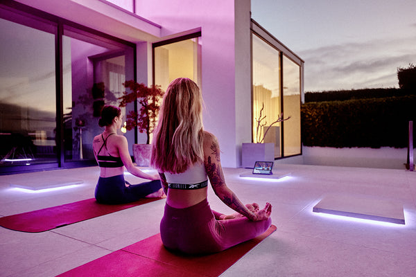 Two girls practising yoga through Les Mills in the evening in their home