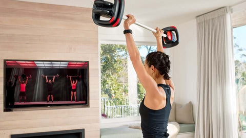 Woman doing a weight exercise with Les Mills SMARTTECH equipment
