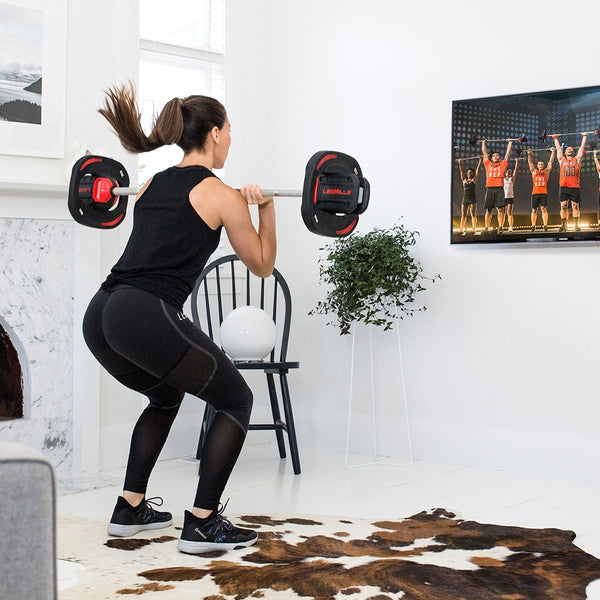 Woman doing the Les Mills Body Pump class at home