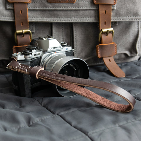 A Due North Leather Racer Camera Wrist Strap attached to an Olympus camera.