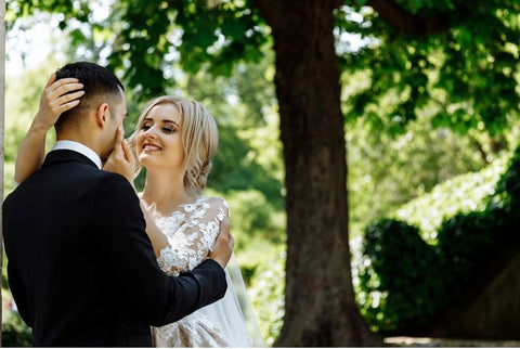 A newlywed couple standing underneath a tree
