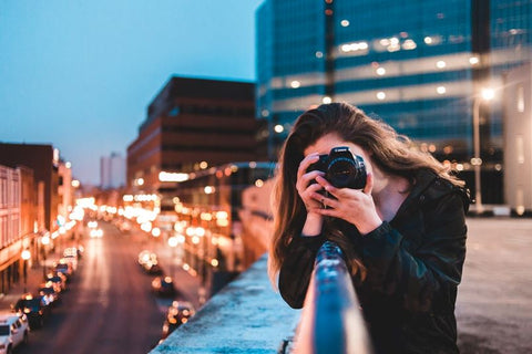 A woman shooting with her camera in a city
