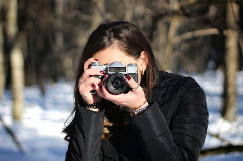 A woman shooting with her camera outdoors