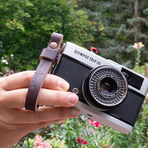 An Olympus film camera with a Due North Leather finger strap attached.