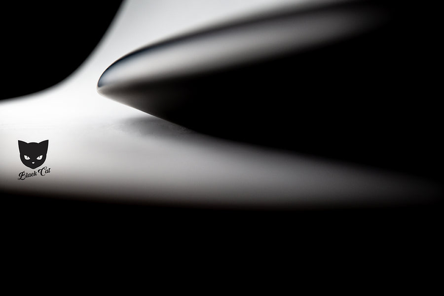 Side profile photo of the rails and bottom contour of a foil surf board