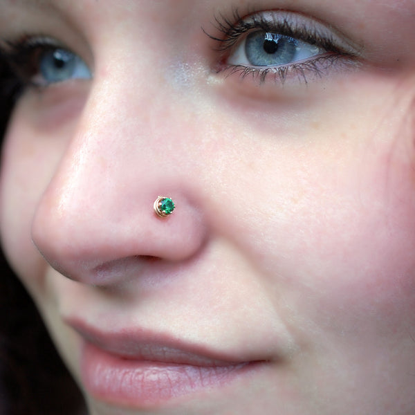 dainty emerald nose stud in 14 karat yellow gold