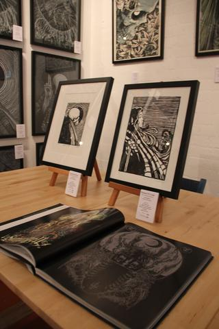 Art work and 'The Art of GODMACHINE Volume 1' on display at The Flood Gallery