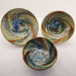 Beautiful bowls glazed with a galaxy swirl in blues, greens, yellows, browns, and reds. Handmade on Vashon Island by Abraham McBride Pottery. Local ceramics artist, Seattle Washington.