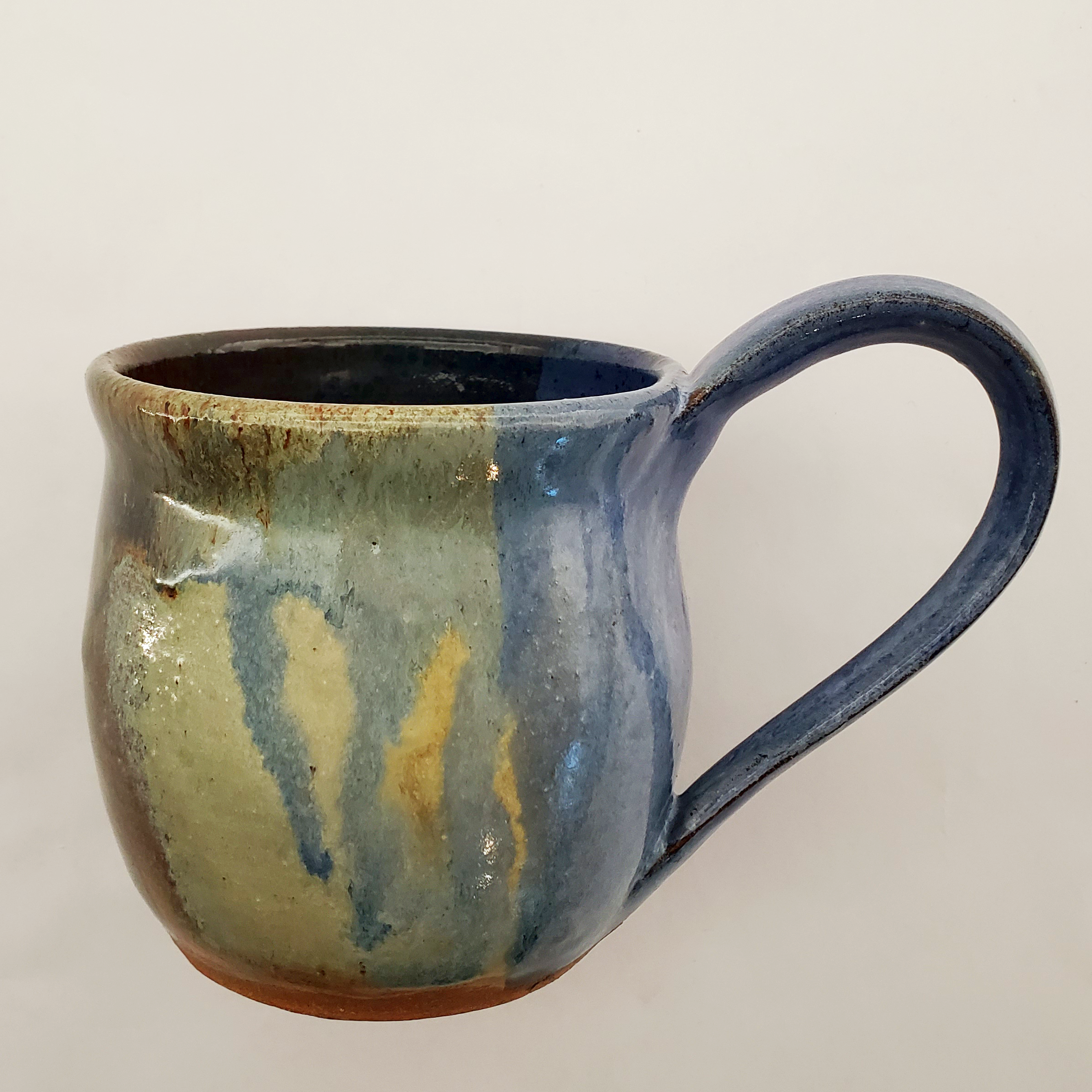 Beautiful handmade mugs in green, blue, red, and orange hues with stylish handles. Handmade on Vashon Island by Abraham McBride Pottery. Local ceramics artist, Seattle Washington.