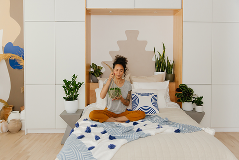 Plant delivered to woman's home sitting on bed with new plant.