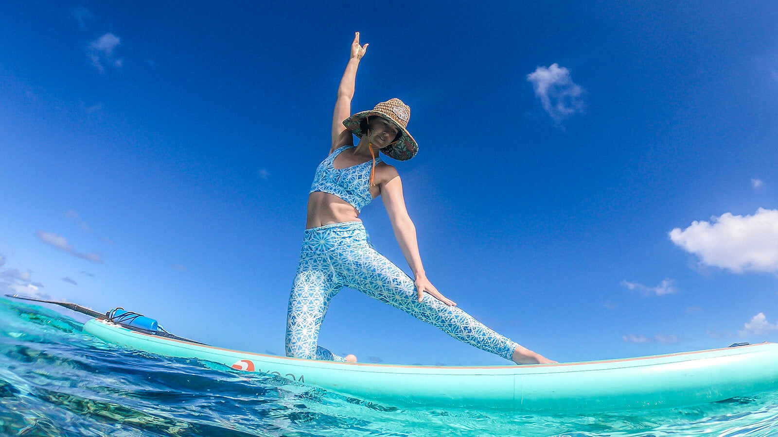 Wolven sustainable activewear, woman in yoga leggings and racerback bra in Aqua Aura print on stand up paddle board