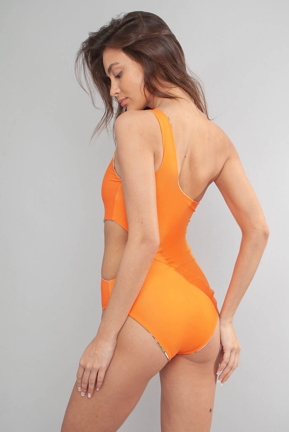 Wolven Flora One Shoulder One Piece Asymmetrical neckline Thick one shoulder strap Mid–coverage bottom Reverses to solid orange Sustainable Swimwear