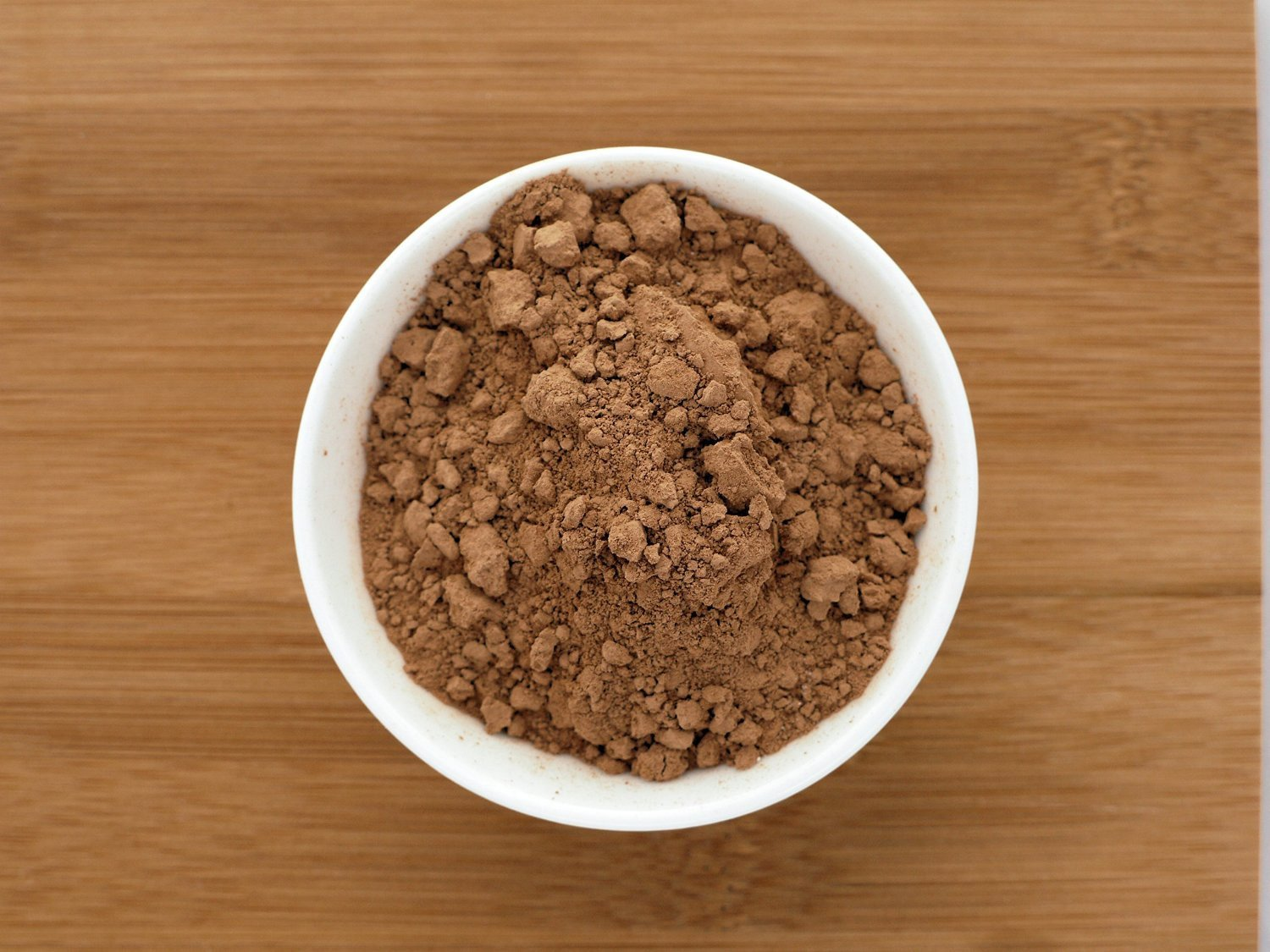 This is an image of a small white bowl containing Cocoa Powder from Anthony's Goods