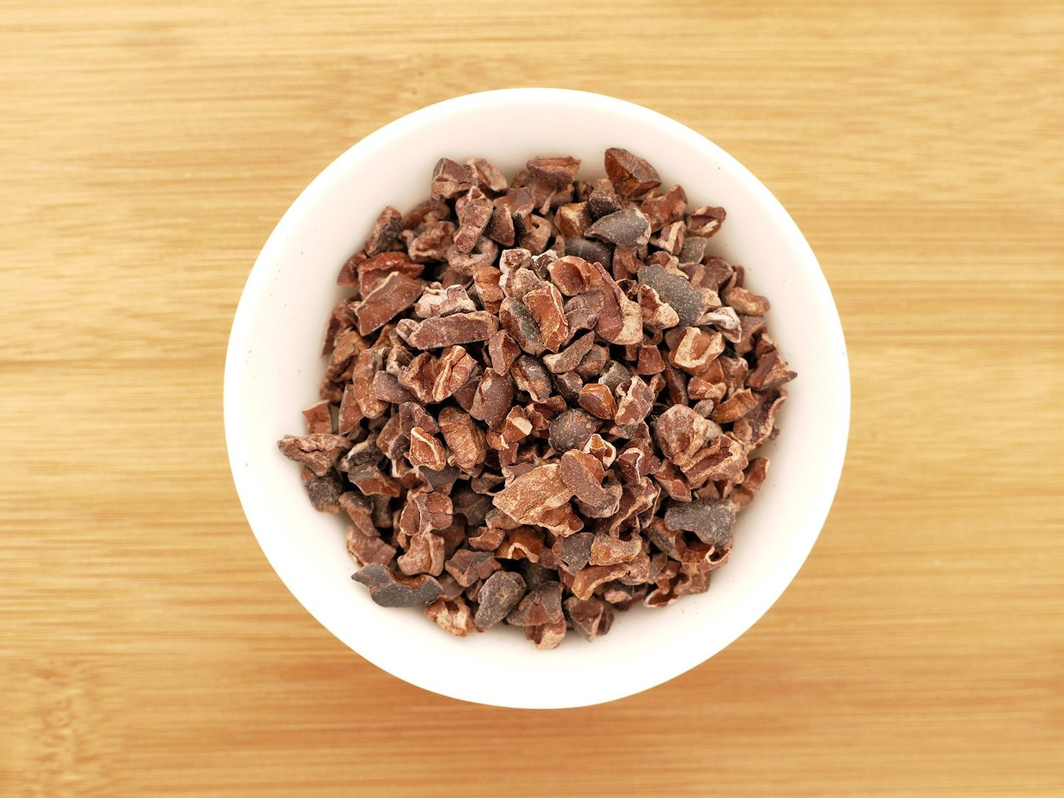 This is an image of a small white bowl containing Organic Cocoa Nibs from Anthony's Goods