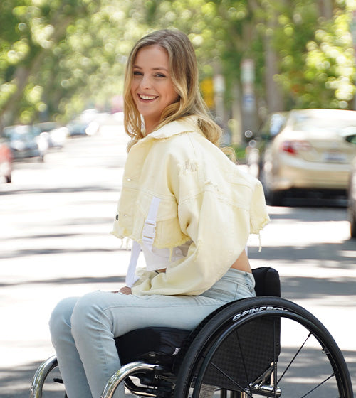 A picture of Catherine Elliott. She's sitting on a wheelchair smiling towards the camera. She is wearing vibrant yellow, spring clothing.