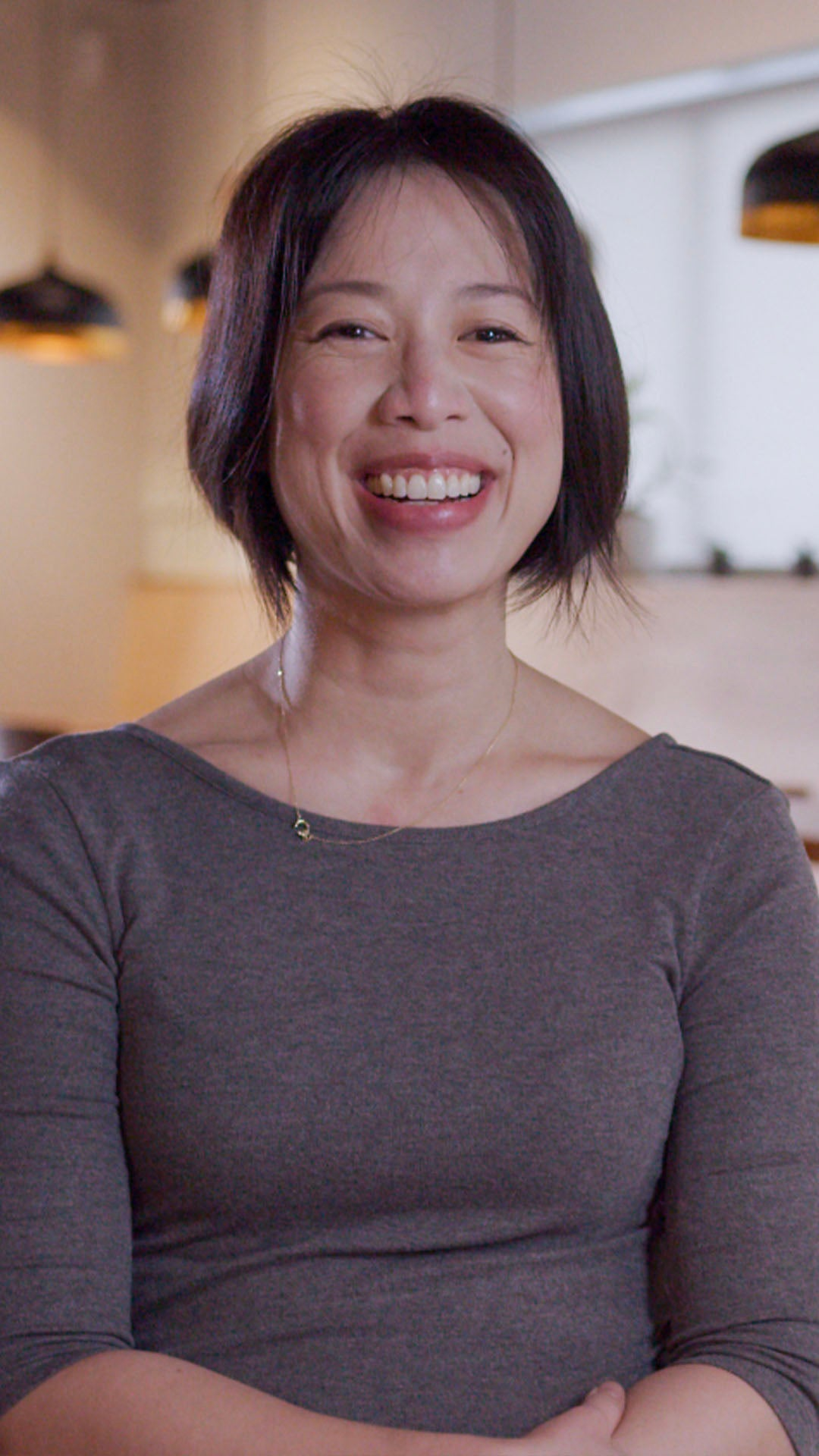 An image of Christine Ha. She is located in her restaurant, Xin Chao. She is smiling happily. Click play to watch video.