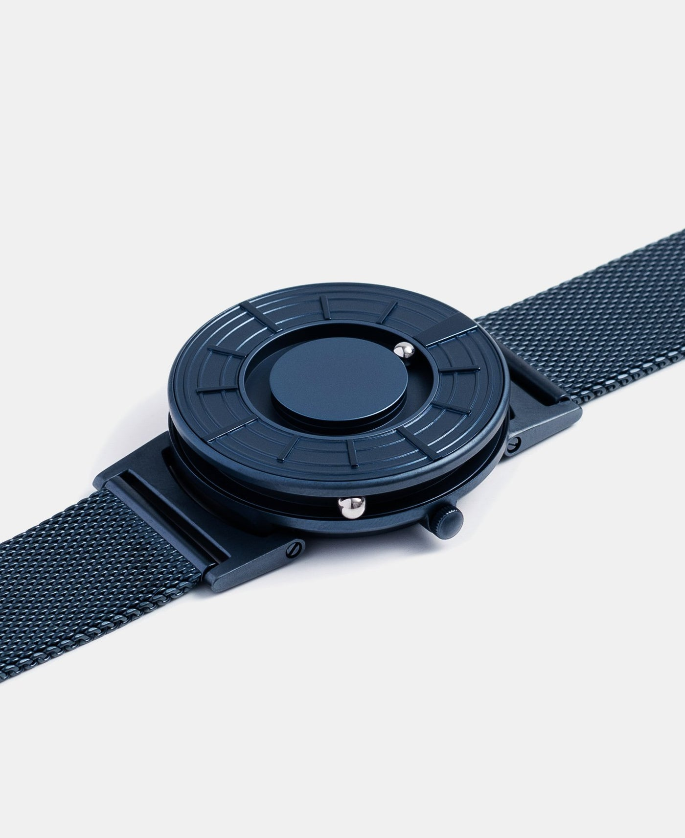 A photo of the watch lying flat on a surface. The recessed track around the outside of the watch face is shown with the hour ball bearing in the track. The raised markers are noticeable from this perspective.