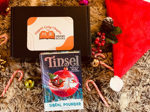 This is a picture of Tinsel as part of our December box of Happier Every Chapter. The copy of Tinsel by Sibeal Pounder is propped up against one of our subscription boxes. The box is black with a large white and orange sticker which displays our logo. Next to the box is a red santa hat. There are some festive-themed decorations and candy canes as part of the image backdrop