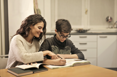 An adult and child sat at their kitchen table reading a book together and doing homework
