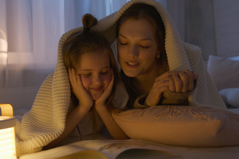 A child and adult laid on their fronts with a blanket over them. They're propping their bodies up using their arms and a cushion and reading a book together