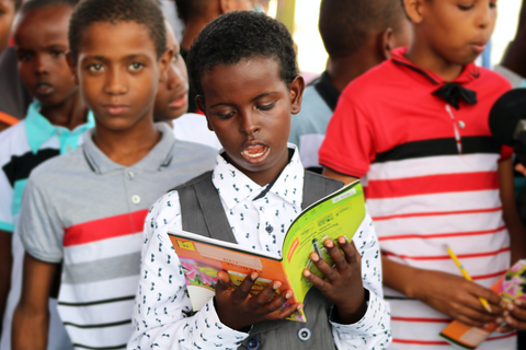 Boy standing in a crowd of other similar-aged boys, reading a book out loud
