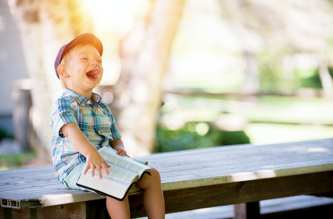 A young boy sitting on a bench. He has a book open on his lap and is hysterically laughing