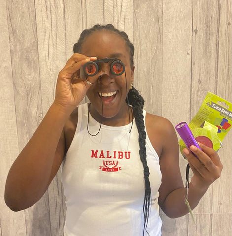 Kirsten holding a pair of mini binoculars to her eyes, with other items in her other hand