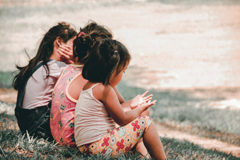 Three young girls sitting in a row. The photo is taken from behind them. They look to be chatting with one another