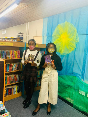 Mbawa Girls holding books from library shelf