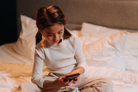 Child on phone in bed