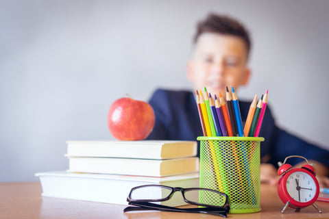 Kid at desk with supplies
