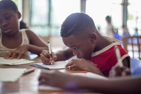 A young boy concentrating on writing in a book at school