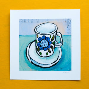 a wonky white teacup on saucer with a blue flower on it and green leaves. the background is pale blue and collaged book pages are visible under the paint