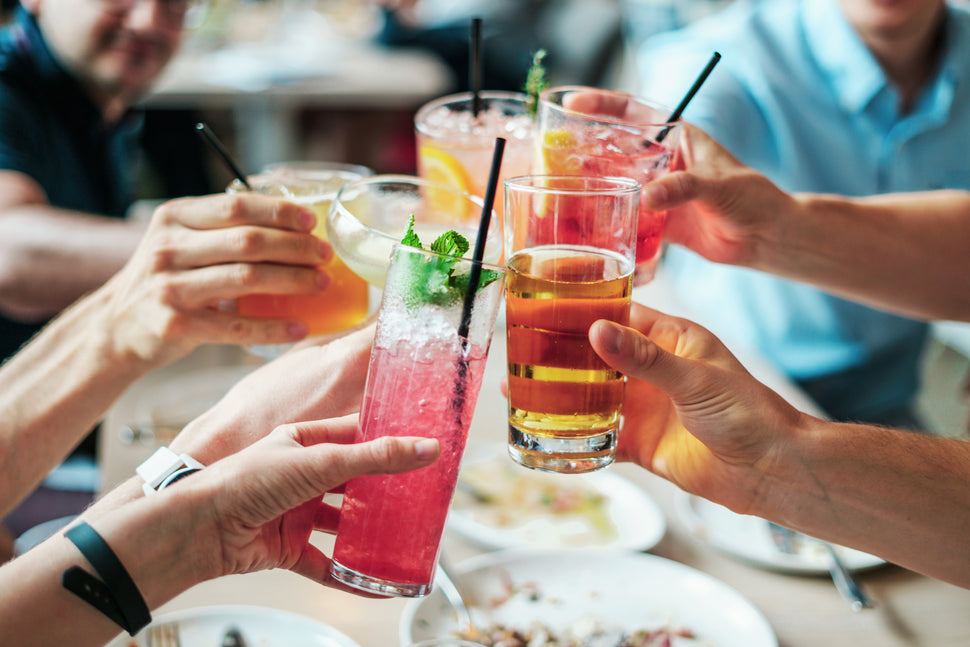 People toasting with drinks and paper straws by Hello Straw