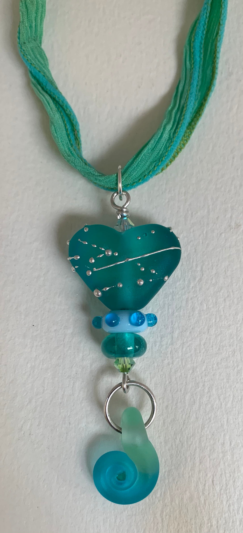 Etched light blue-green heart with spiral, silver and silk ribbon