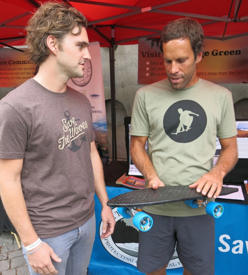 Bureo co-founder Ben Kneppers hands Jack a skateboard prototype at his 2014 concert in Santiago, Chile