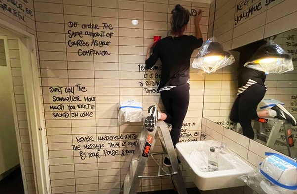 Female painter painting black words on white toilet wall