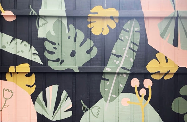 outdoor fence mural featuring pink, green and yellow leaves