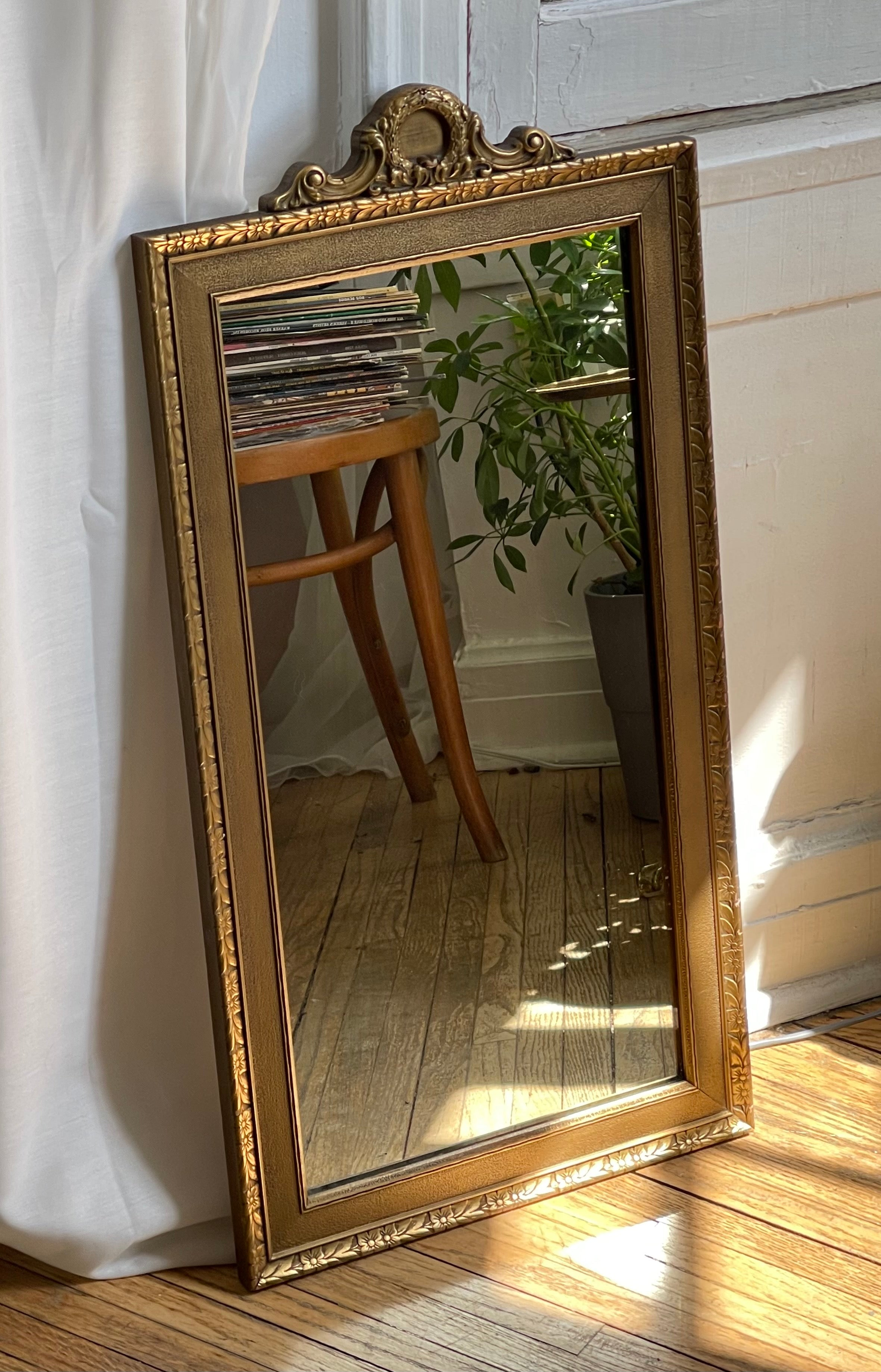 vintage, ornate gold-framed mirror