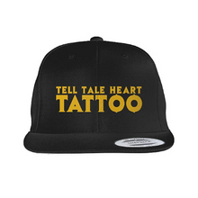 Load image into Gallery viewer, Tell Tale Heart Tattoo Logo embroidered in gold on a black flat bill hat.