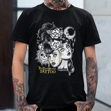Load image into Gallery viewer, Two Headed Lady Monster on black t-shirt on a tattooed male model. Black and white with gold tears.