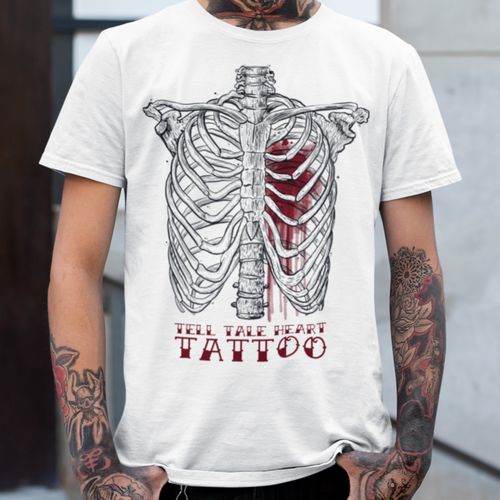 Black ribcage with exploded red heart on white shirt with the words Tell Tale Heart Tattoo in Red tattoo style font on a white t-shirt worn by a tattooed male model.