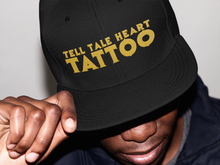 Load image into Gallery viewer, Tell Tale Heart Tattoo Logo embroidered in gold on a black flat bill hat worn by a male model.