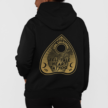 Load image into Gallery viewer, Tell Tale Heart Planchette Design on back of black hoodie worn by female model.