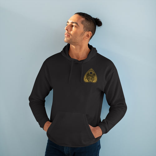 Tell Tale Heart Planchette Design on left front breast of black pullover hoodie worn by male model with hands stuffed in kangaroo pocket.