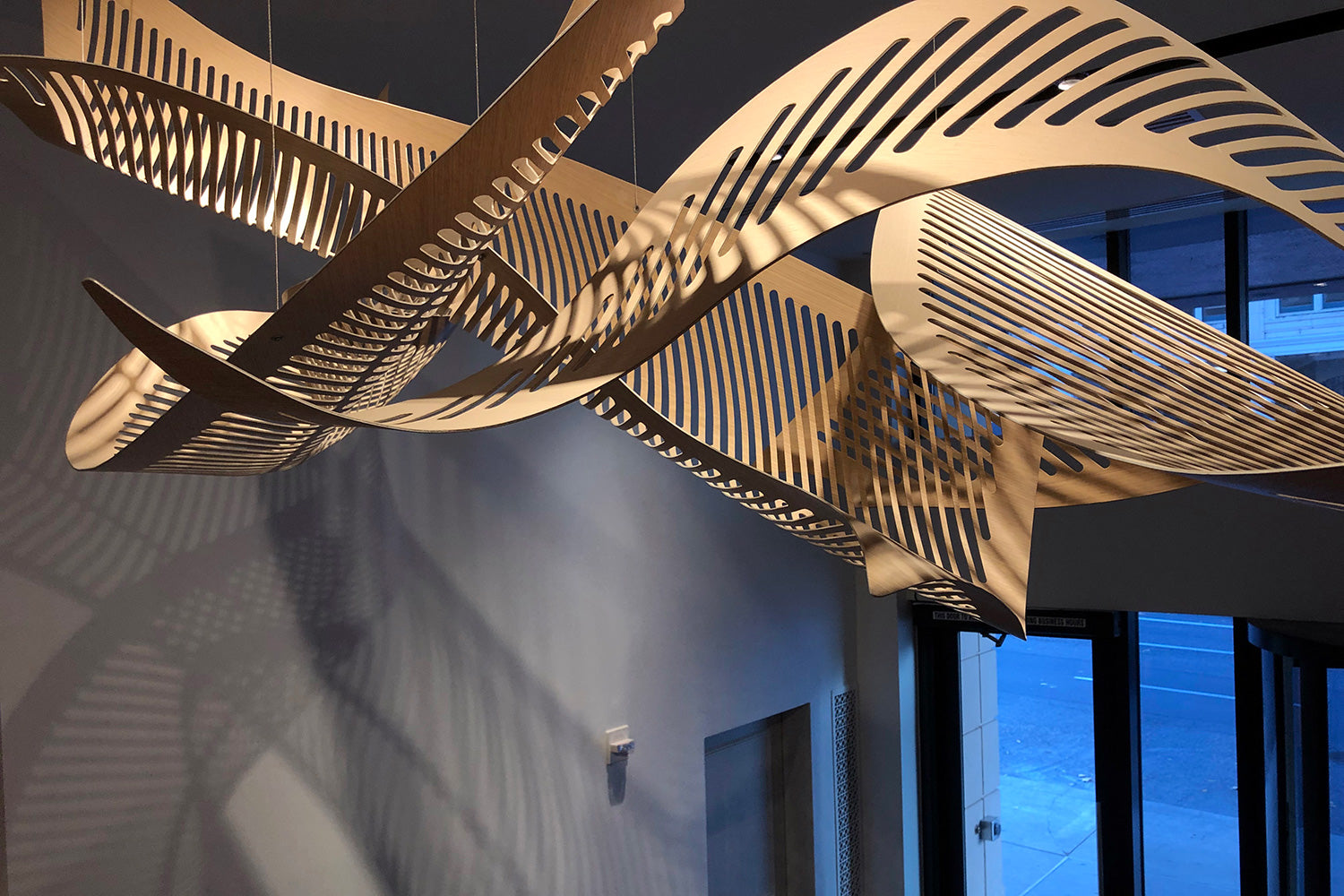 Twisted wood sculpture hanging from a ceiling